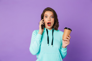 Shocked emotional young woman posing isolated over purple background wall.