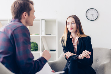 selective focus of businesswoman in suit giving interview to journalist and looking at him in office