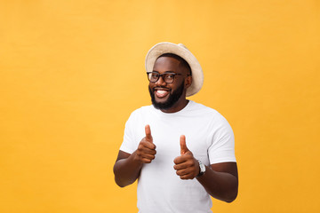 Image of cheerful young african man standing and posing over yellow background with thumbs up. Looking at camera