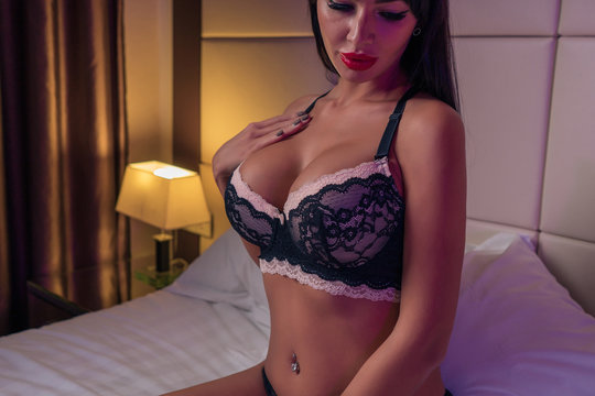 Beautiful slim girl with big sexy breasts poses on a bed in a hotel
