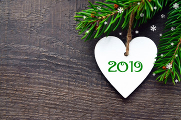2019 New Year greeting card.Decorative white wooden heart and fir tree branch on old wooden background with copy space.Winter holidays concept.Selective focus.