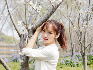 Outdoor portrait of beautiful young Chinese girl smiling among blossom cherry tree brunch in spring garden, beauty, summer, emotion, expression and people lifestyle concept.