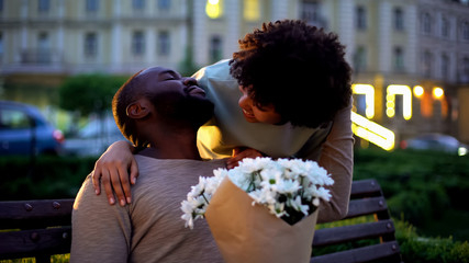 Lady embracing boyfriend, looking with love, holding flowers, romantic date