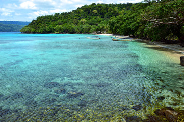 Remote and tranquil beach in Pulau Weh, Indonesia. Crystal clear water and lush green water front.