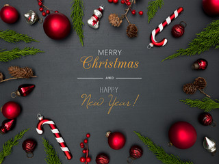 christmas background with lettering merry christmas, with frame with red baubles, green branches and other christmas items on blackboard