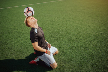 Picture of football playr sitting on knees on lawn and hold ball on forehead. He looks up. Guy makes no move. He is concentrated. It is sunny outside.
