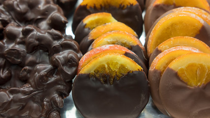 Chocolate covered candied orange slices displayed at the baker shop, prepared for winter holidays. Delicious Christmas treat, dry nuts and caramelized orange slices dipped in dark and milk chocolate