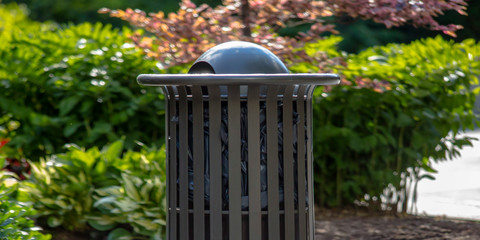 Outdoor trash can with plants in the background