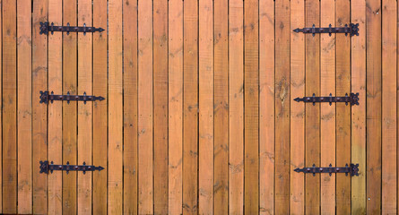 The texture of the wooden fence with wrought iron elements