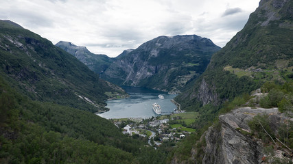 Vantage, spectacular views of Geiranger village, one of the most picturesque places at the head of Geirangerfjord, towards the surrounding mountains and cliffs, the village and the fjord, in Norway