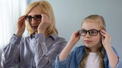 Little blond girl putting eyeglasses, wants to look like grandmother, family
