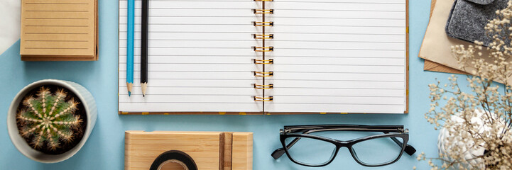 Panoramic top view of modern bright blue office desktop with notebook, school supplies on table, empty space for text, cactus, glasses, flowers. Back to school concept on the blue background..