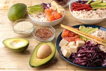 poke bowl Hawaiian food. a plate of rice, salmon, avocado, cabbage and cheese. next to sesame and fresh avocado on a natural wooden table