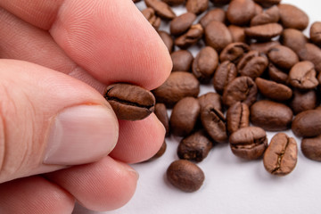 Hand holding a coffee bean between the fingers. Food and drink  background