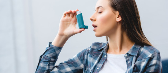 girl using inhaler while suffering from asthma at home
