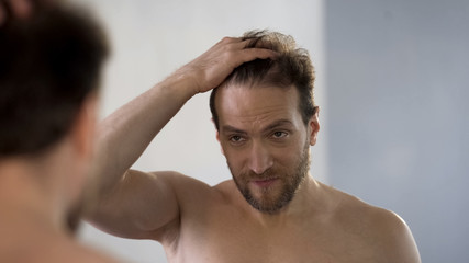 Worried man looking in mirror at his bald patches, hair loss problem, hygiene Wall mural