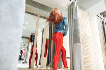 red-haired girl measures red leather pants. beautiful woman reflected in the mirror. lady buys clothes
