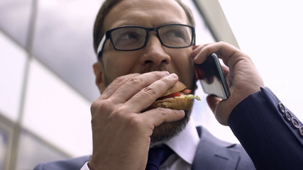 Unhealthy nutrition, busy businessman talking on phone and eating burger lunch