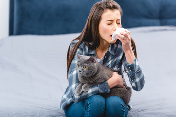 young woman with allergy holding facial tissue and british shorthair cat at home