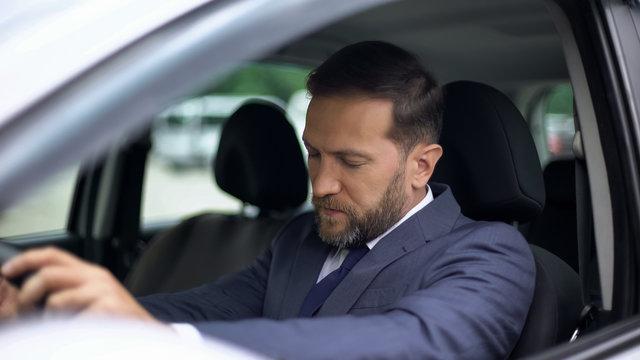 Sleepy businessman in car, morning hangover, feeling dizzy, accident risk