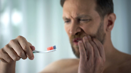 Male in bathroom looking at blood toothbrush, oral hygiene, parodontosis illness Wall mural