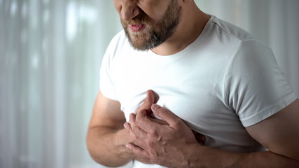 Man in 40s feeling strong chest pain, heart attack caused by stress, cardiology