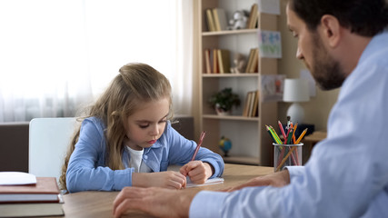 Caring father helping his little daughter doing homework, home schooling