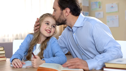 Proud father doing homework together with his daughter, education, family care