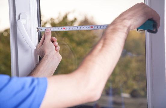 Man measuring window. Installing new window in house