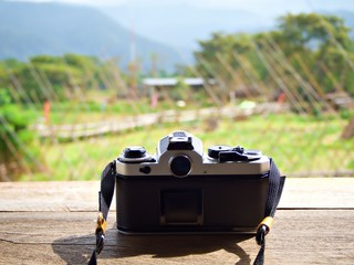 Vintage film camera stand on the wooden table with blur nature background in Nan, Thailand