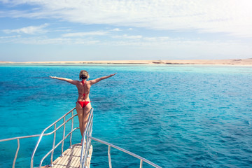 Woman relaxing at cruise ship's nose with open arms on sea background .