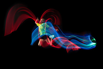 The one caucasian young teenager girl playing badminton at studio. The female teen player on black background in motion with flashes of light