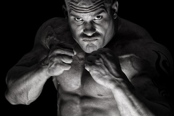 Bare knuckle fighter in front of black background