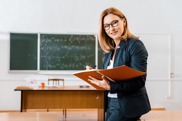 Obraz beautiful female teacher in formal wear writing in notebook and looking at camera in classroom - fototapety do salonu
