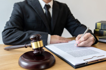 Legal law, advice and justice concept, male counseling lawyer or notary working on a documents and contract papers of the important case and wooden gavel, brass scale in courtroom