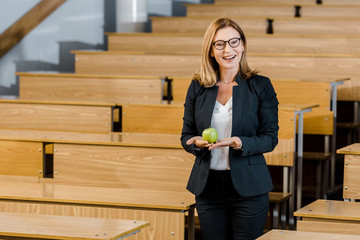 smiling female teacher in glasses and formal wear holding apple and looking at camera in classroom
