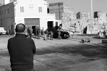 man watching the workers of the marina of Peniche in black and white
