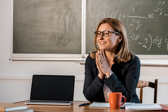 smiling female teacher sitting at computer desk with blank screen in classroom
