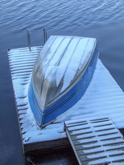snow covered aluminum boat upside down on dock