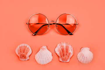 Summer flatlay with round gradient sunglasses and sea shells on the bright living coral backfround.