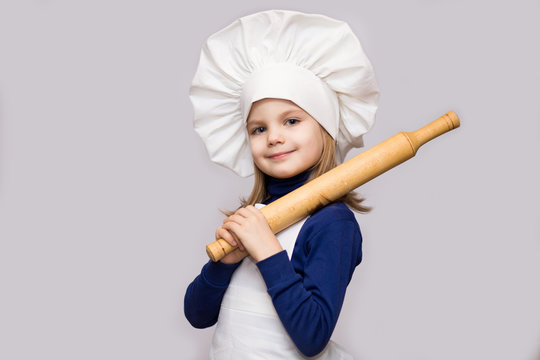 Children cook. Happy little girl in chef uniform holds rolling pin isolated on white background.