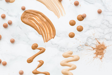 Samples of skin tone cosmetics on marble surface