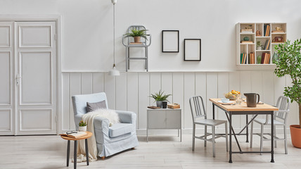 Decorative dining room and living room, white door, wooden wall, frame and lamp, armchair with coffee table and wooden dining table style. White shelf and home object.
