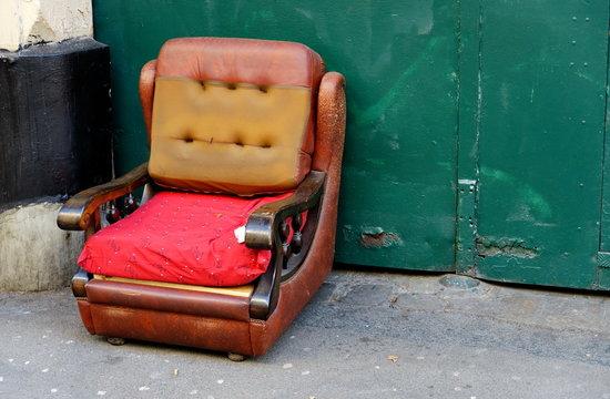 Vieux fauteuil en cuir jeté dans la rue. encombrants