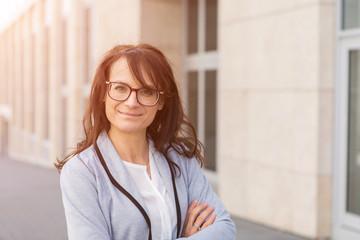 Smiling Businesswoman Wearing Eyeglasses Outside Office Building