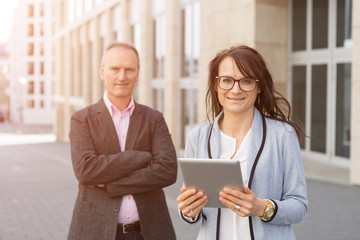 Confident Businesswoman Holding Digital Tablet By Colleague In City