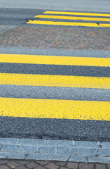 Yellow painted zebra crossing markings on a road