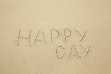 handwritten inscription happy day made in the sand, text on the beach