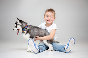 Portrait of a joyful little boy having fun with siberian husky puppy on the floor at studio. The animal, friendship, love, pet, childhood, happiness, dog, lifestyle concept