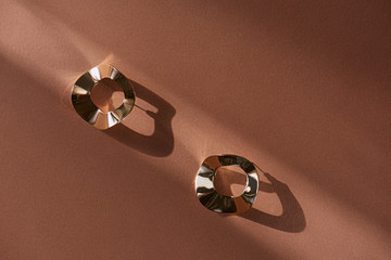 top view of beautiful luxury golden earrings on brown surface with sunlight